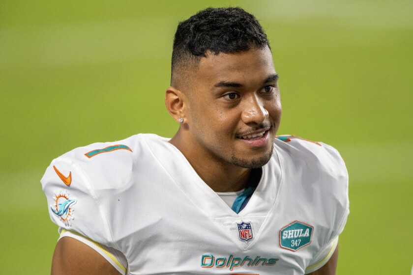 FILE - This Oct. 18, 2020, file photo shows Miami Dolphins quarterback Tua Tagovailoa (1) on the sidelines before playing for the first time against the New York Jets during an NFL football game, in Miami Gardens, Fla. Tagovailoa's winning personality helped the Miami Dolphins avoid locker room backlash when he was promoted to replace popular veteran Ryan Fitzpatrick. (AP Photo/Doug Murray, File)
