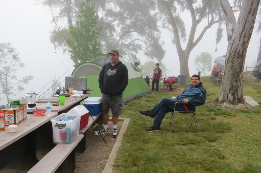 Scott Kellhofer (left) and Eric Heidemann relax around their campsite at Lake Poway Saturday morning.
