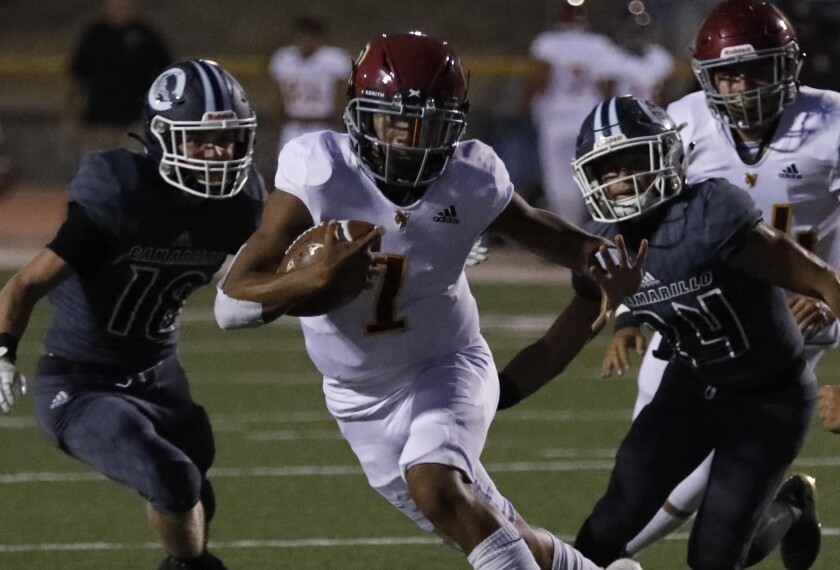 Oxnard quarterback Jaden Jones runs past Camarillo defenders to score a touchdown on Friday.