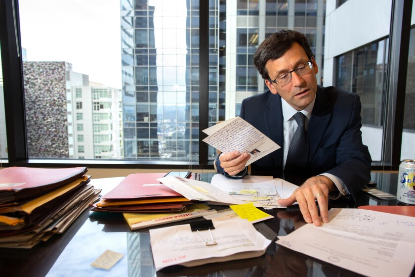Ferguson, shown in his Seattle office on Sept. 19, leafs through letters that he's received concerning his lawsuits against the Trump administration.