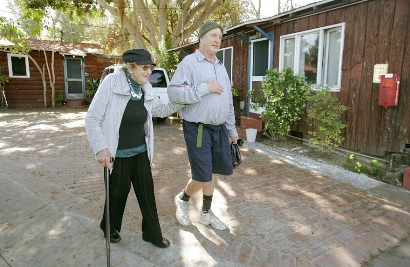 At the Log Cabin Apartments, longtime tenant William Reagan walks with Jeanne Fuller through the small complex along North Coast Highway 101 in Leucadia. In 1962, Fuller and her late husband bought the motel and it hosted a wide-ranging clientele, from young servicemen to jockeys, surfers and vacat