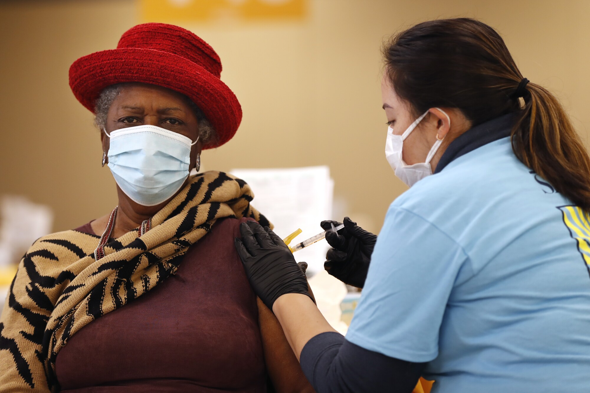 Earline Hilliard gets a COVID-19 vaccine shot from Tiffany White at the Sharp South Bay Super Station on Thursday.