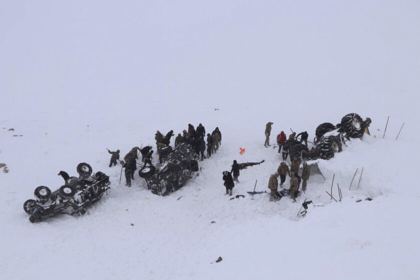 Emergency service members dig in the snow around at least three overturned vehicles, near the town of Bahcesehir, in Van province, eastern Turkey, Wednesday, Feb. 5, 2020. Some dozens of rescue workers are missing after being hit by a second avalanche while on a mission to find two people missing in a previous snow-slide that struck late Tuesday, burying a snow-clearing vehicle and a minibus.( DHA via AP)