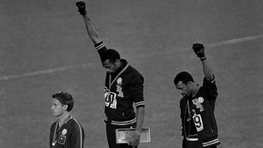 "United States athletes Tommie Smith, center, and John Carlos, right, during the playing of the ""Star-Spangled Banner"" after collecting gold and bronze medals at the 1968 Summer Olympic Games in Mexico City. The IOC wants to ban such silent protests at this summer's games in Tokyo."