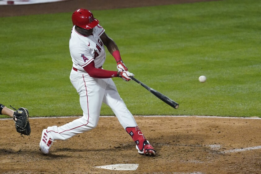 Los Angeles Angels left fielder Justin Upton (10) hits a home run during the eighth inning of a baseball game against the Chicago White Sox Saturday, April 3, 2021, in Anaheim, Calif. Jared Walsh also scored. (AP Photo/Ashley Landis)