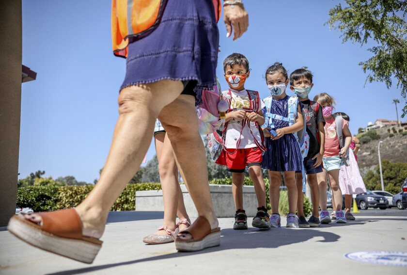 Los estudiantes de kindergarten caminan a clase en la Sunset Hills Elementary School en Poway