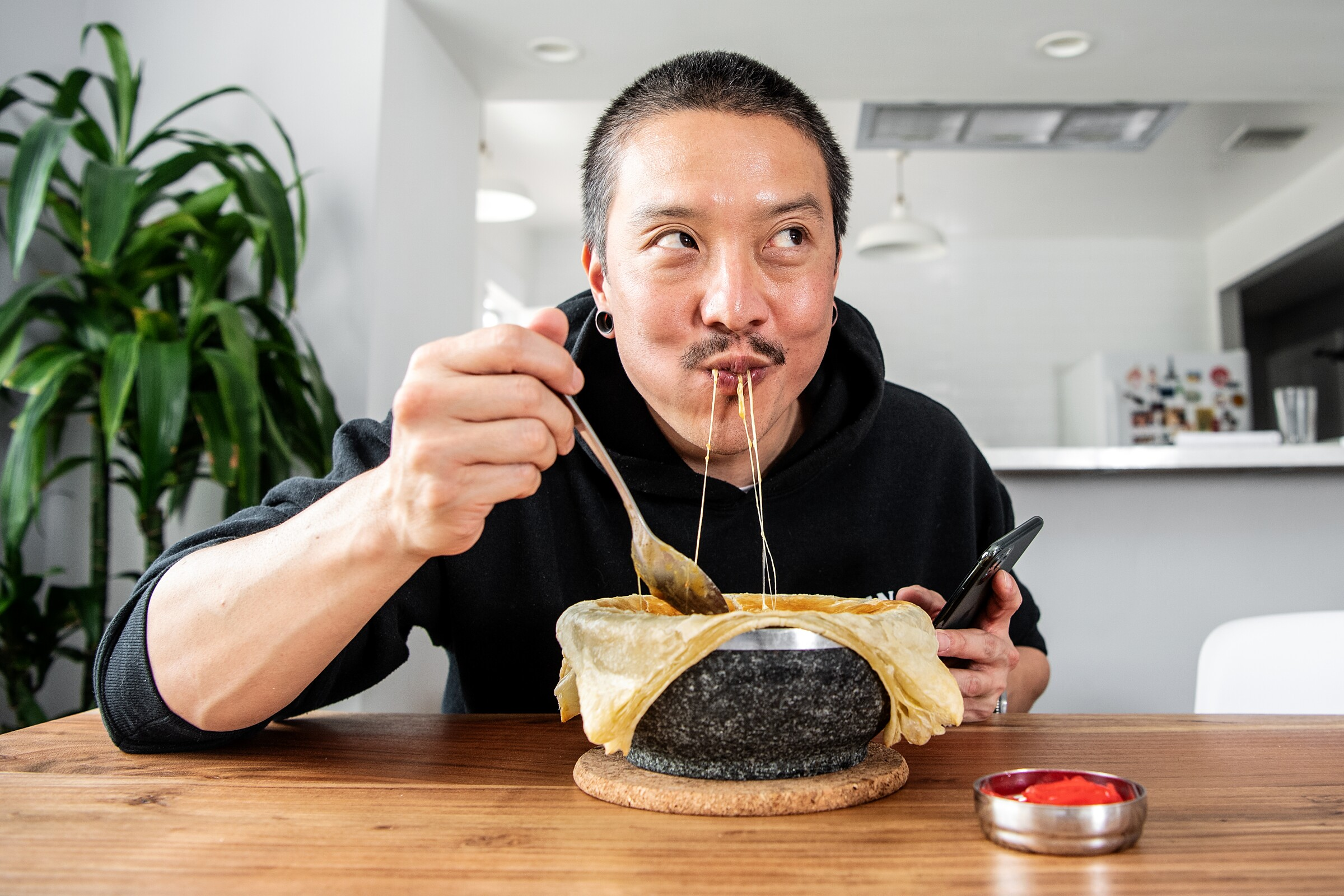 Chef Chris Oh tastes a recent dish, cheesy Japanese curry chicken pot pie, at his home in Los Angeles. During the stay-at-home order, Oh has used the time to create and post numerous videos of his cooking.