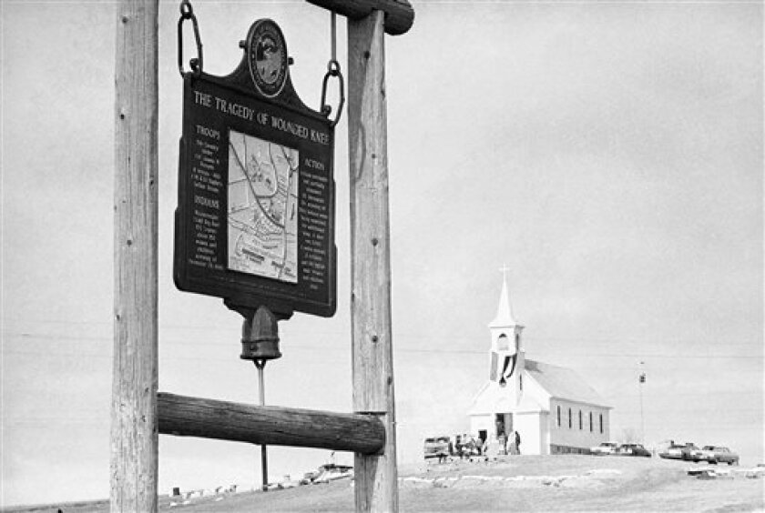 FILE - This undated file photo shows the historical marker commemorating the Wounded Knee Massacre of 1890 on the road near the Sacred Heart Catholic Church in Wounded Knee, S.D. Wednesday is the final day a landowner has given the Oglala Sioux Tribe to make an offer to buy a portion of the Wounded Knee National Historic Landmark. James Czywczynski has said he would sell the land, which sits next to where about 150 of the 300 Lakota men, women and children killed by the 7th Cavalry in 1890 are