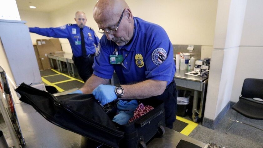 FILE - In this Nov. 21, 2014 file photo, a TSA agent checks a bag at a security checkpoint area at M