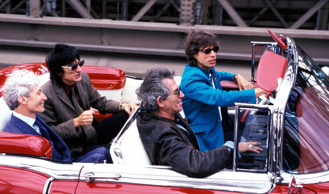 Mick Jagger drives Charlie Watts, Ron Wood and Keith Richards in a convertible car.