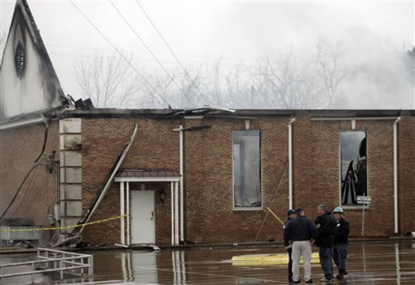 FILE - In this Feb. 4, 2010 file photo, investigators talk in front of the burned Russell Memorial United Methodist Church in Wills Point, Texas. The seventh church fire this year in east Texas destroyed the sanctuary of the church. A federal official says a fire that destroyed a church last week was the eighth case of arson against a house of worship in Texas this year. (AP Photo/Mike Fuentes, File)