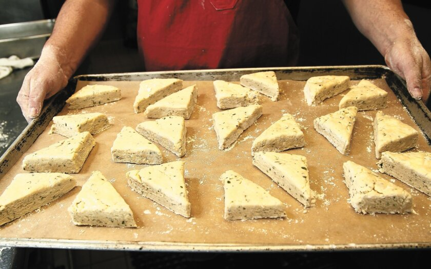 The biscuit dough is cut into triangles and baked on a parchment-lined baking sheet.