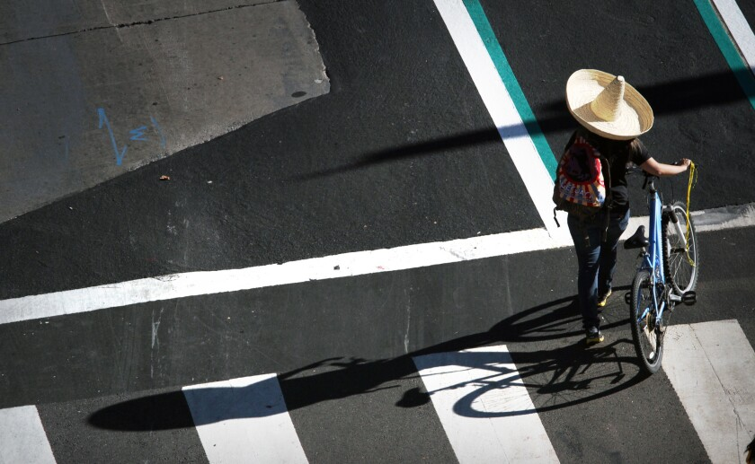 A pedestrian walks her bike in downtown Los Angeles to join fellow cyclists at the eight edition of the CicLAvia bike festival.