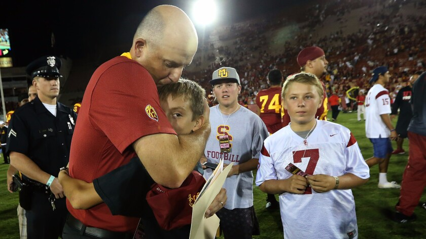Interim USC coach Clay Helton kisses his son, Turner, at midfield after the Trojans beat Utah 42-24 at the Coliseum on Oct. 24, 2015.