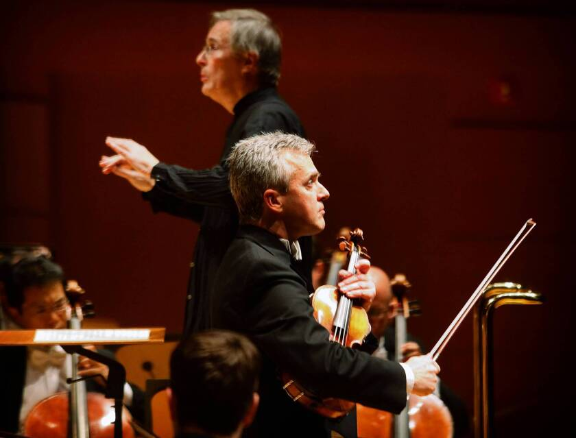 Christian Zacharias, background, conducts the L.A. Philharmonic on Nov. 29, 2013. Concertmaster Martin Chalifour, foreground, is the soloist in a familiar Bach concerto and a small Schubert rarity.