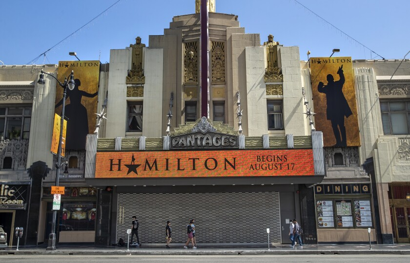 """Pedestrians walk past the closed Hollywood Pantages Theatre, whose marquee promotes """"Hamilton."""""""