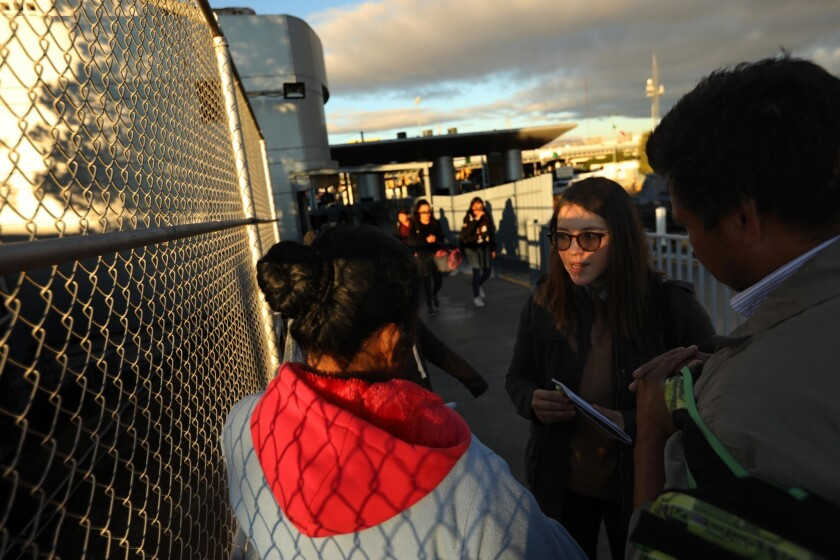 Edith Tapia, a policy research analyst with the Hope Border Institute, center, talks with a Mexican couple and their children who hope to request asylum in the U.S. at the foot of an international Bridge in Ciudad Juarez, Mexico.