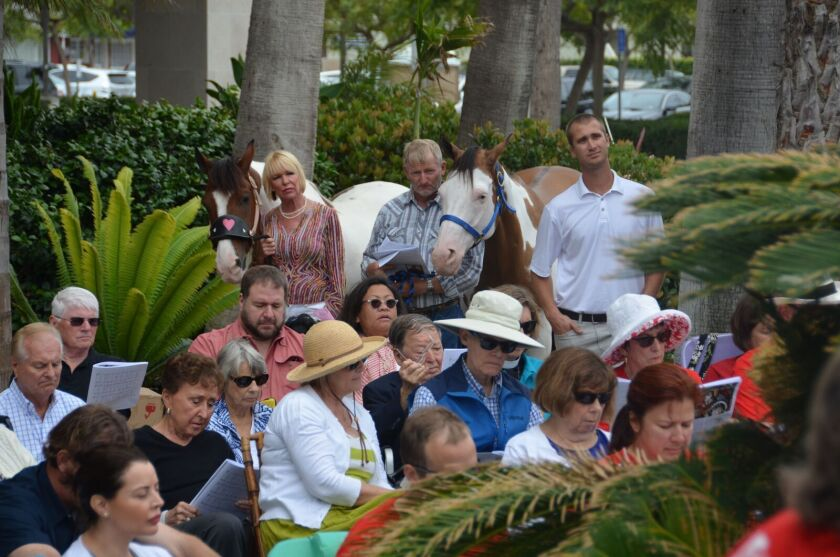 Parishioners, some with their animals, attend Sunday services at a park near St. James church on Lido Isle in July.