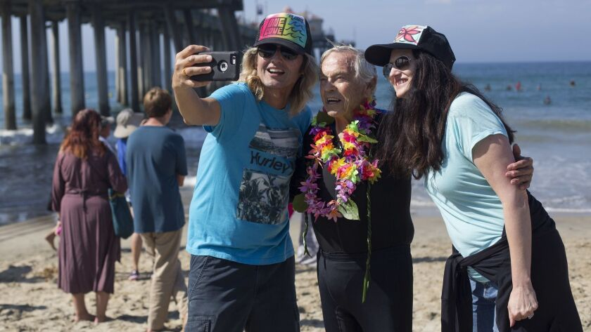 The Rev. Christian Mondor, center, poses for a photo during last year's Blessing of the Waves in Huntington Beach.