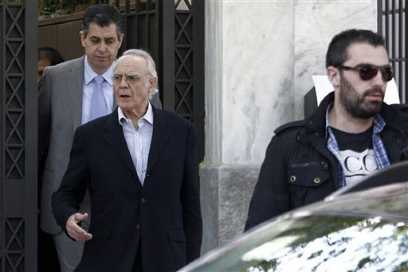 Police officers in plain clothes arrest Former Greek Socialist defence minister Akis Tsochadzopoulos, second right, from his house in central Athens, on Wednesday, April 11, 2012. Tsochadzopoulos was arrested following a judicial investigation into alleged money laundering in connection with a submarine contract.(AP Photo/Petros Giannakouris)