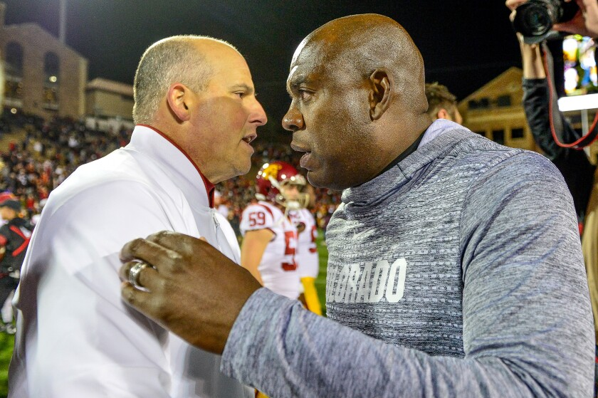 USC coach Clay Helton, left, and Colorado coach Mel Tucker meet on the field after the Trojans' 35-31 win Friday.
