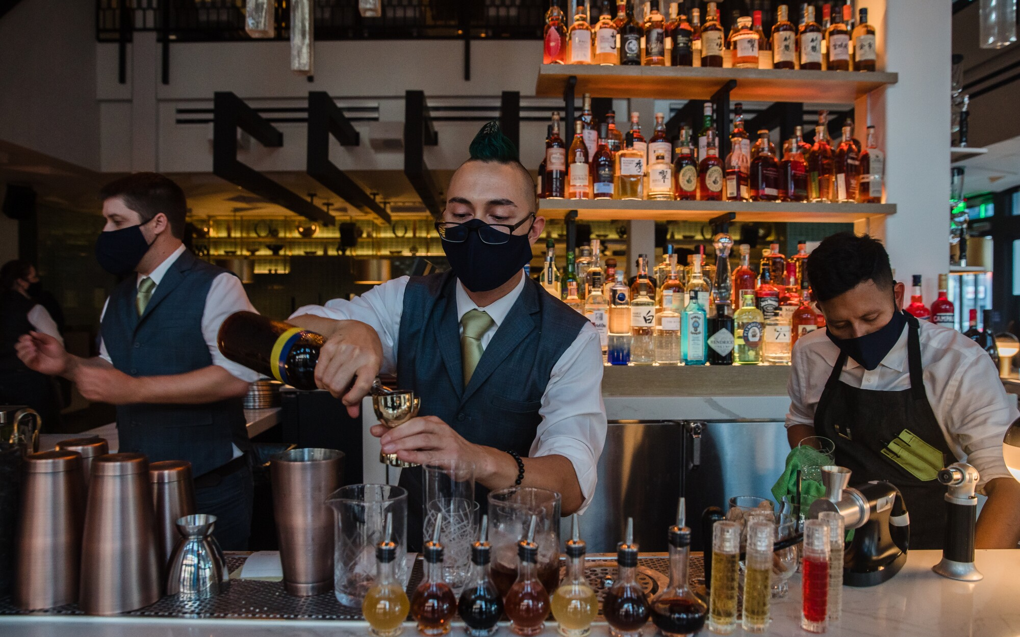 Nick Hirsch, center, prepares a drink at the Huntress, during a soft opening Thursday evening in the Gaslamp Quarter.