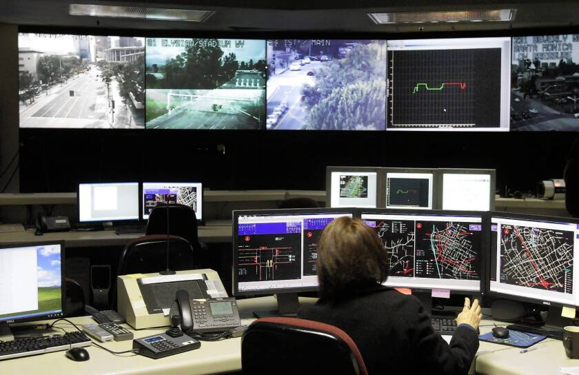 City engineers keep an eye on congestion at the traffic surveillance center under the City Hall annex. All L.A. signals are now under central control.