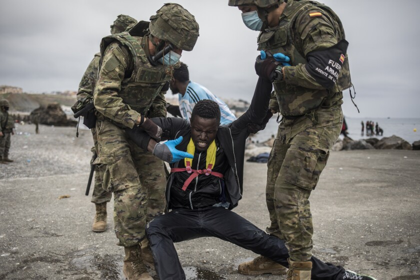 A man from Morocco is detained by soldiers of the Spanish Army at the border of Morocco and Spain