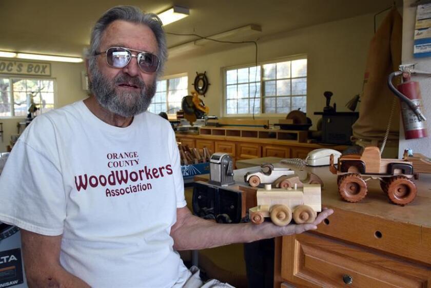 El miembro de la organización no lucrativa Orange County Woodworkers de California, Ken Crandall, de 75 años, posa mostrando un juguete de madera este 18 de diciembre de 2018 en el taller de carpintería en la casa de Ken Crandall en Anaheim, California (EEUU). EFE