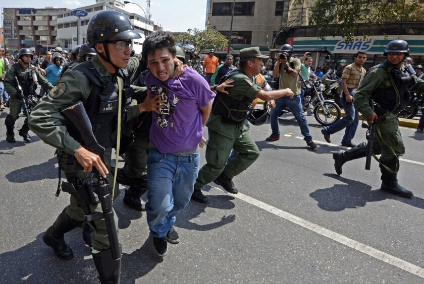 Venezuelan National Guard members in Caracas arrest a demonstrator during a protest against the government of President Nicolas Maduro and to protect him from being attacked by pro-Maduro motorcyclists.