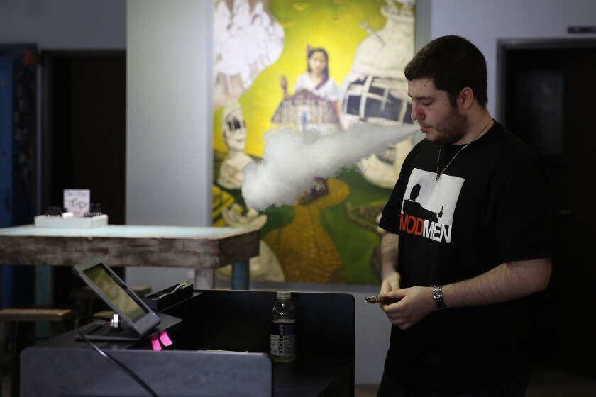 Reese Flores, owner, smokes an e-cigarette at Vapegoat in Highland Park last year.