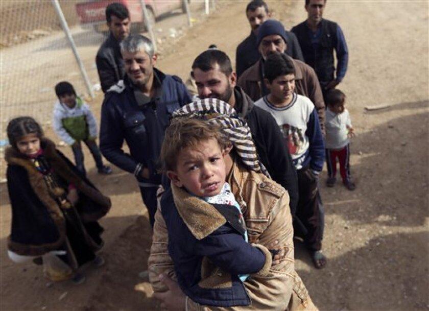 Refugiados iraquíes de los combates en Mosul esperan que se les entregue ayuda humanitaria el 5 de diciembre del 2016 en Khazir, Irak.