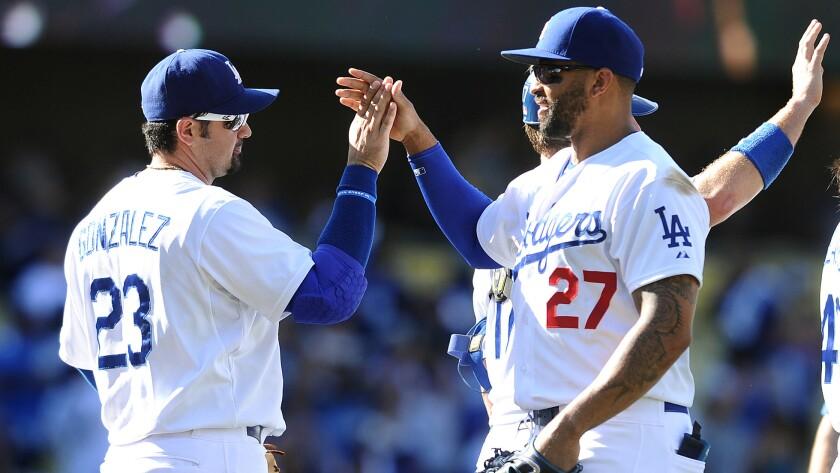 Dodgers teammates Adrian Gonzalez, left, and Matt Kemp celebrate a 7-2 win over the Arizona Diamondbacks on Sunday.