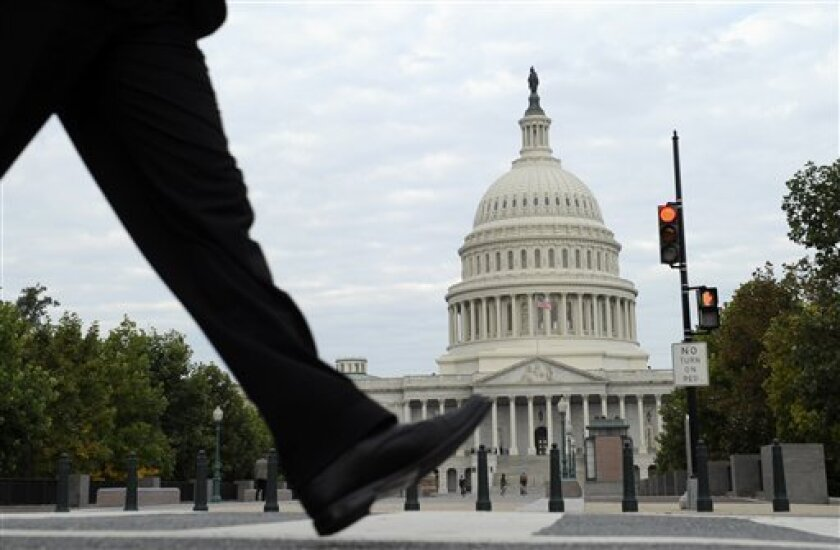 People walk near Capitol Hill in Washington, Tuesday, Oct. 1, 2013.  Congress plunged the nation into a partial government shutdown Tuesday as a long-running dispute over President Barack Obama's health care law stalled a temporary funding bill, forcing about 800,000 federal workers off the job and