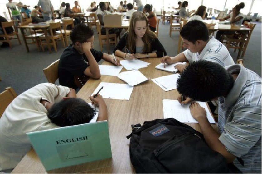 In the peer-tutoring program at Scripps Ranch High School, Omar Moreno (from left) and Gerardo Diaz, both 15, were helped with algebra by fellow  student Lauren Trott. On the right were Enrique Calzada (top), 15, and Ralph Agustin, 14.