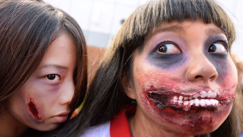 Participants make up as they pose for pictures before the Halloween Parade in Kawasaki, a suburb of