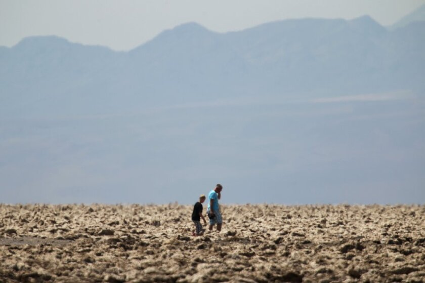 Tourists walk in an area known as The Devil's Golfcourse in Death Valley. Scientists have found that a cyanobacterium that helps stabilize desert soil is imperiled by climate change.