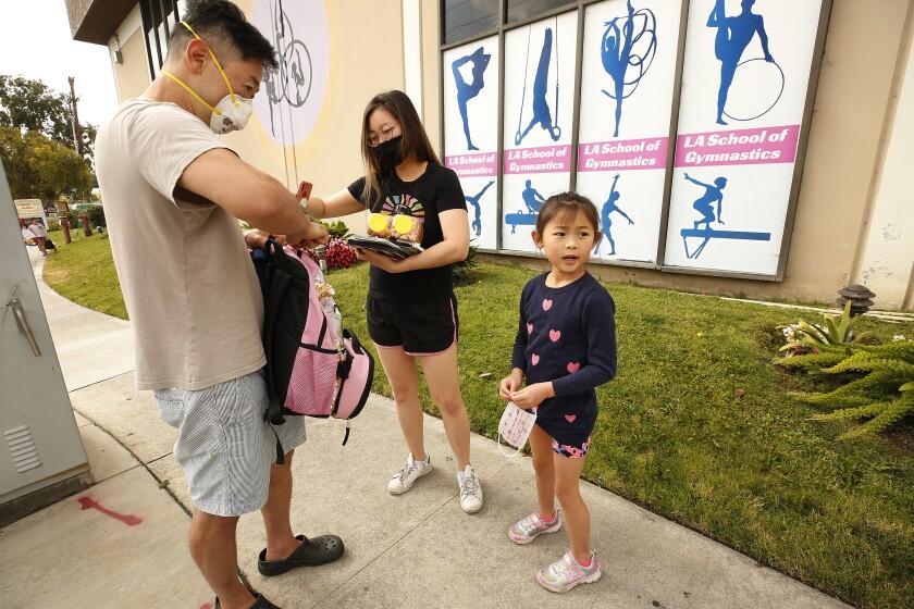 Shawn Chou and Jennifer Lee drop off their daughter Samantha Chou, 6, at LA Gymnastics in Culver City
