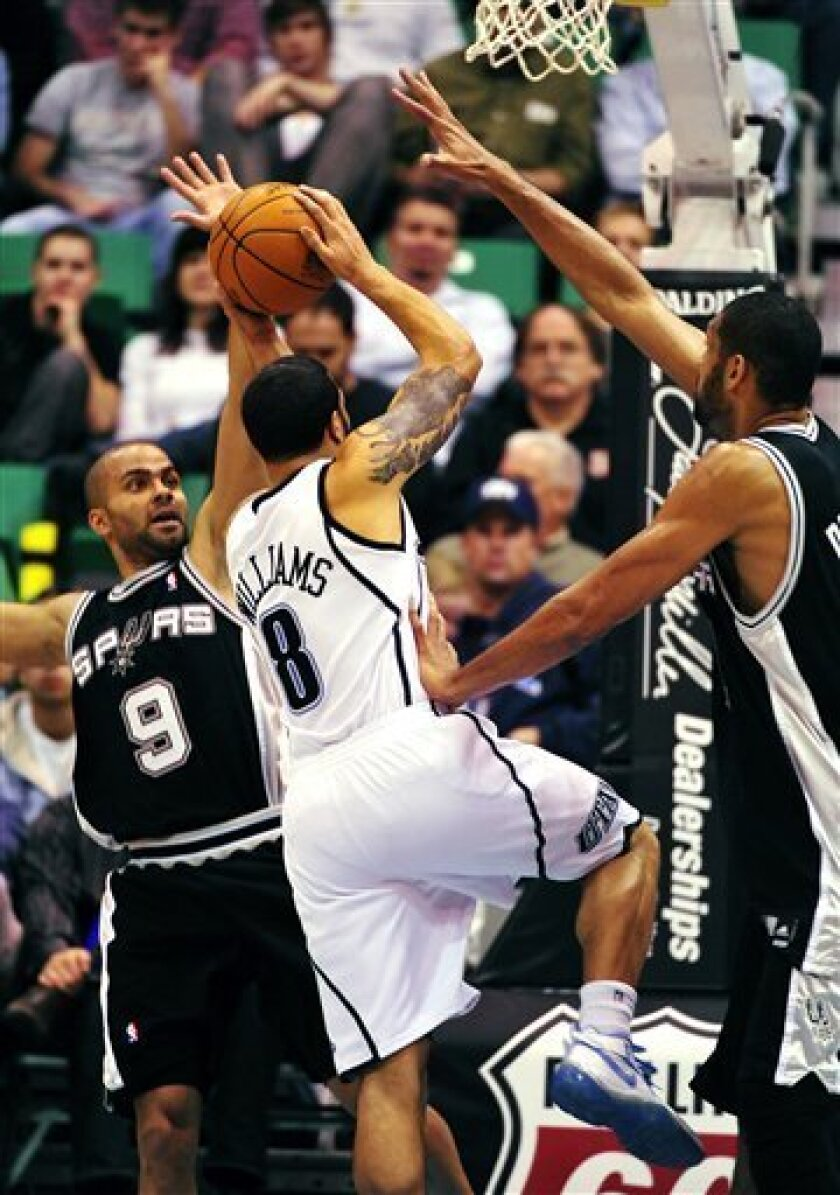 Utah Jazz guard Deron Williams (8) drives to the hoop as he is guarded by San Antonio Spurs guard Tony Parker (9) and Tim Duncan during the first half of an NBA basketball game Monday, Dec. 7, 2009, in Salt Lake City. (AP Photo/Danny Chan La)