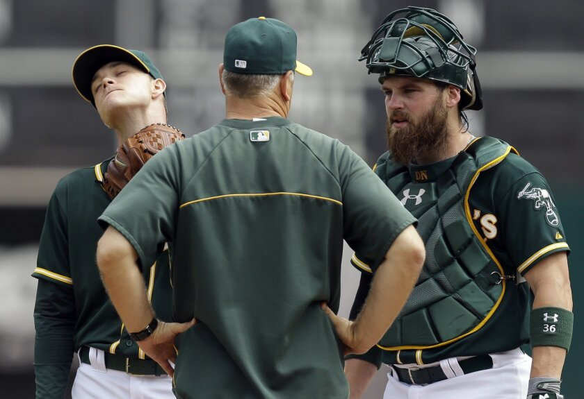 Oakland Athletics' Sonny Gray, left, is visited by pitching coach Curt Young, center, and catcher Derek Norris in the first inning of a baseball game against the Texas Rangers Thursday, Sept. 18, 2014, in Oakland, Calif. (AP Photo/Ben Margot)