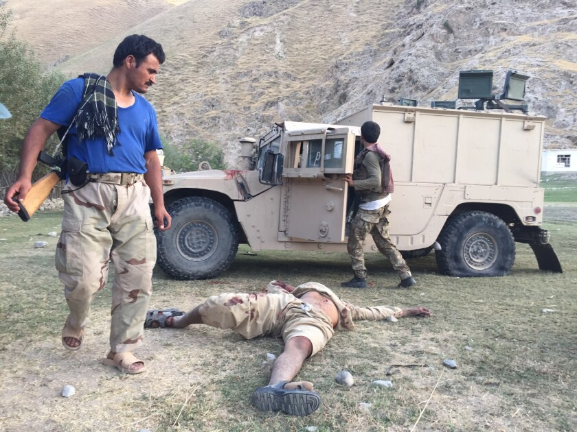 An Afghan policeman, left, stands over the body of a suspected Taliban leader killed in a July battle in Eshkamesh, Afghanistan.