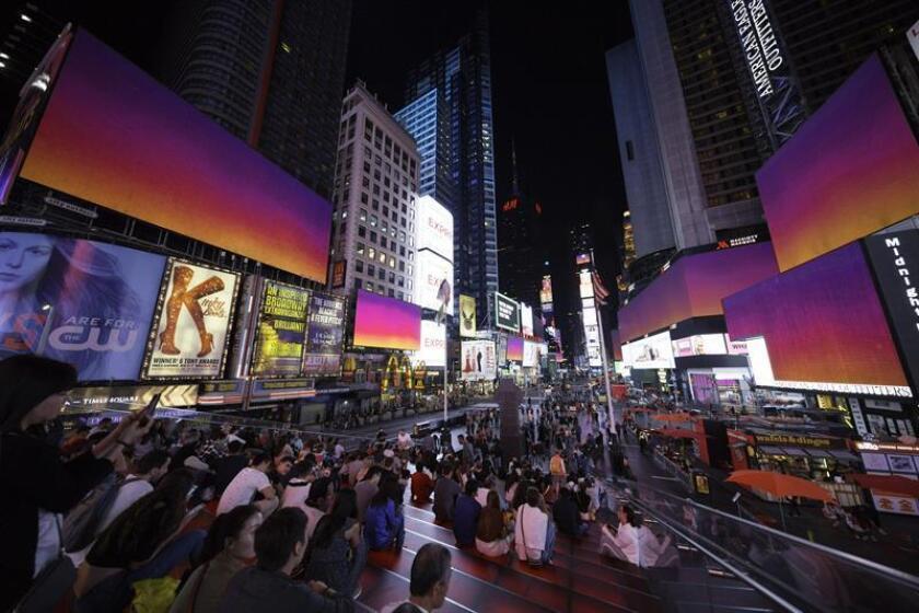 """Fotografía cedida por Times Square Arts, fechada el 1 de octubre de 2018, donde se aprecia a unos visitantes del icónico sector turístico de Times Square en Nueva York mientras disfrutan de un """"amanecer digital"""" a través de sus gigantescas pantallas, obra de la artista española Isabel Martínez que quiere regalarles tres minutos de paz. EFE/Ka-Man Tse/Times Square Arts/SOLO USO EDITORIAL/NO VENTAS/CRÉDITO OBLIGATORIO"""
