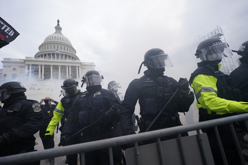 Police stand guard in riot gear near the Capitol while smoke is in the air.