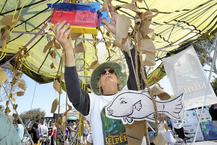 Artist Mike Beanan hangs up a fish, made from a cardboard box, as he helps set up a kelp forest during Kelpfest 2013 at Main Beach.