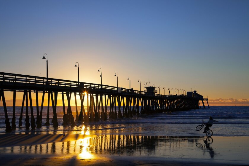 A bicycle rider enjoying the low tide in Imperial Beach cruises his bike near Imperial Beach Pier.