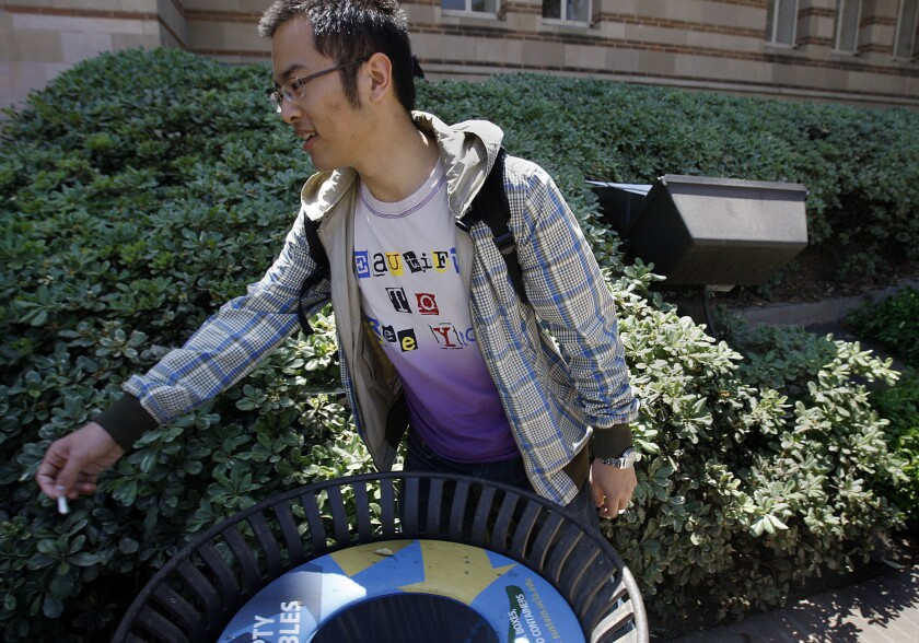 Hejia Yan, 23, throws away his cigarette butt on the campus of UCLA in 2013 on the first day of a tobacco ban on the campus. State lawmakers want to increase the tobacco tax.