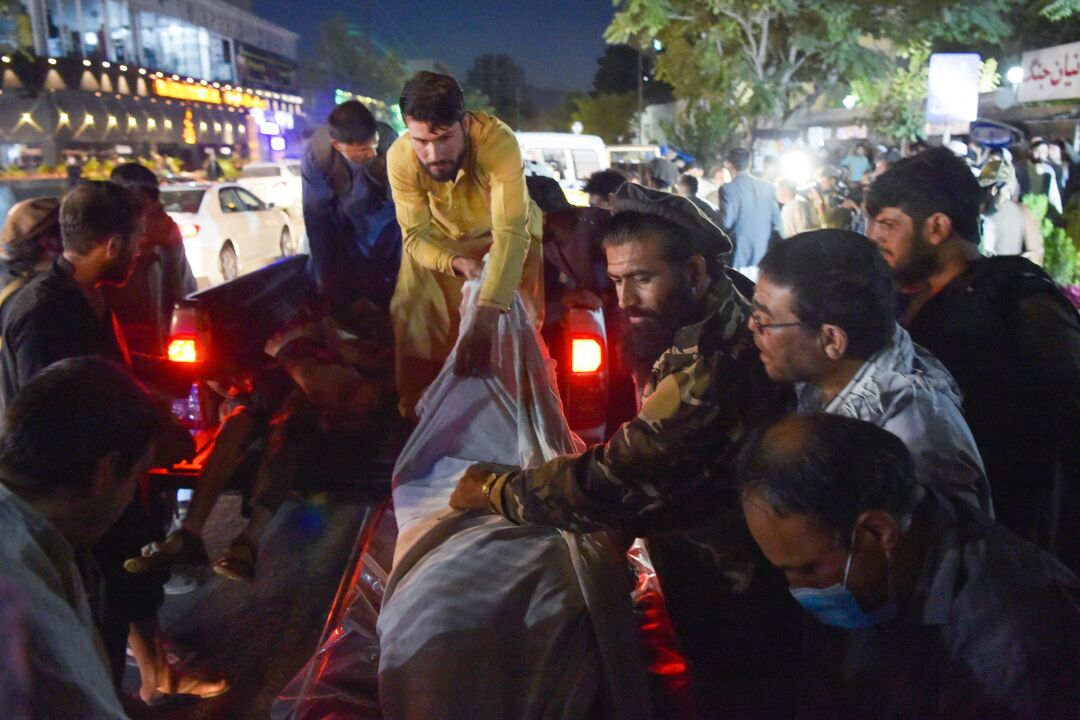 Volunteers and medical staff unload bodies from a pickup truck outside a hospital