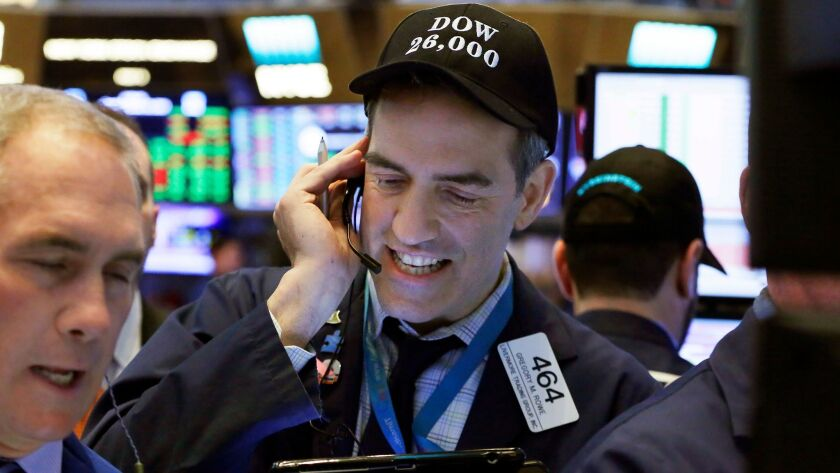 "Trader Gregory Rowe wears a ""Dow 26,000"" hat on the floor of the New York Stock Exchange."