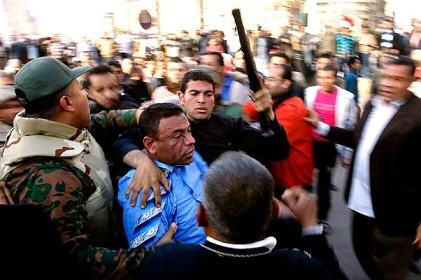 A pro-Mubarak supporter is set upon by those favoring regime change.