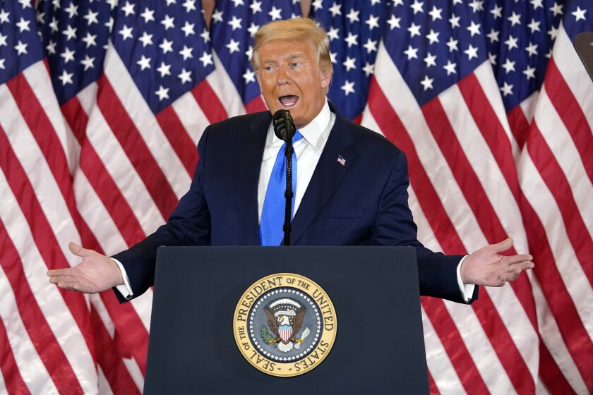 President Trump gestures with both hands while speaking at a lectern with the presidential seal in front of U.S. flags